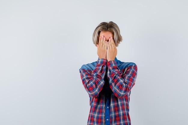 Jovem rapaz adolescente com camisa, cobrindo o rosto com as mãos e parecendo deprimido, vista frontal.