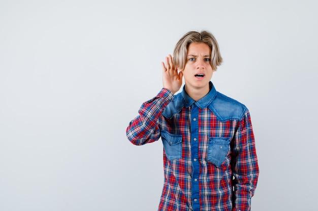 Jovem rapaz adolescente com camisa xadrez, mantendo a mão atrás da orelha e parecendo confuso, vista frontal.
