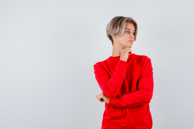 Jovem rapaz adolescente com suéter vermelho olhando para o lado com o queixo apoiado na mão e olhando com foco, vista frontal.