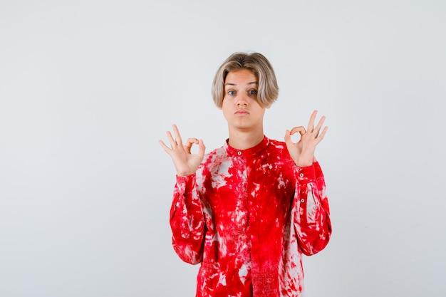 Jovem rapaz adolescente em camisa mostrando o gesto de ok e olhando espantado, vista frontal.