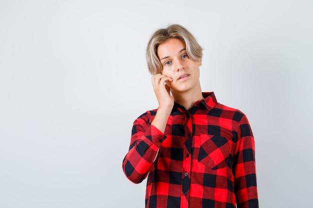 Jovem rapaz adolescente em camisa xadrez com a mão na bochecha e olhando confiante, vista frontal.
