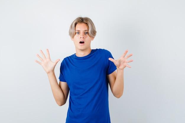 Jovem rapaz adolescente em t-shirt azul, mostrando o gesto de rendição e olhando com medo, vista frontal.
