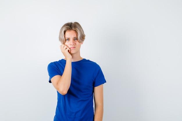 Jovem rapaz adolescente em t-shirt azul, sofrendo de dor de dente e parecendo incomodado, vista frontal.