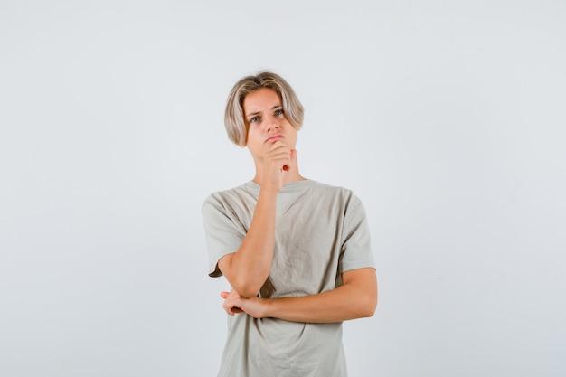 Jovem rapaz adolescente em t-shirt, mantendo a mão no queixo, olhando para cima e olhando pensativo, vista frontal.