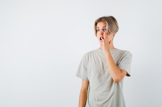 Jovem rapaz adolescente em t-shirt, mantendo a mão perto da boca aberta enquanto olha para longe e parece chocado, vista frontal.