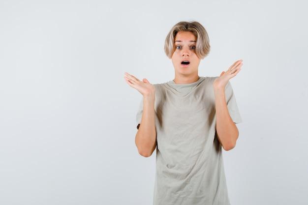 Jovem rapaz adolescente em t-shirt, mostrando um gesto desamparado e parecendo desnorteado, vista frontal.