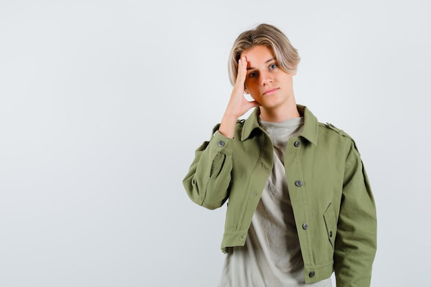 Jovem rapaz adolescente inclinando a cabeça por lado na t-shirt, jaqueta e parecendo chateado. vista frontal.