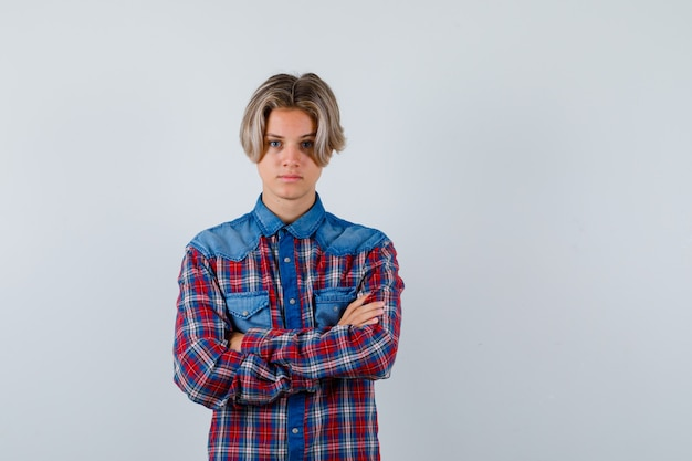 Jovem rapaz adolescente mantendo os braços cruzados em uma camisa e olhando sério. vista frontal.