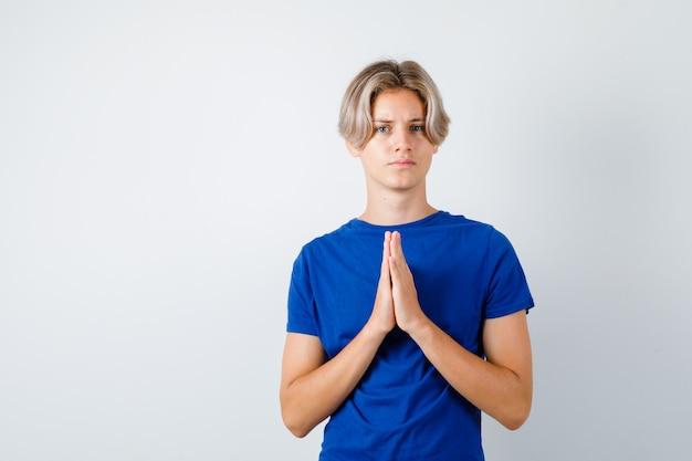 Jovem rapaz adolescente mostrando as mãos postas em gesto de súplica em t-shirt azul e parecendo incerto. vista frontal.