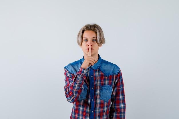 Jovem rapaz adolescente mostrando o gesto de silêncio na camisa e olhando com cuidado. vista frontal.