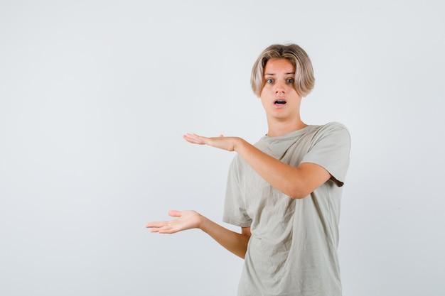 Jovem rapaz adolescente mostrando sinal de tamanho em t-shirt e olhando surpreso, vista frontal.