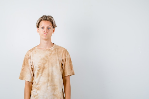 Jovem rapaz adolescente olhando para frente enquanto fazia careta na camiseta e parecendo desapontado. vista frontal.