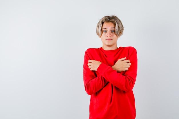 Jovem rapaz adolescente segurando os braços cruzados no peito em uma camisola vermelha e parecendo apavorado. vista frontal.