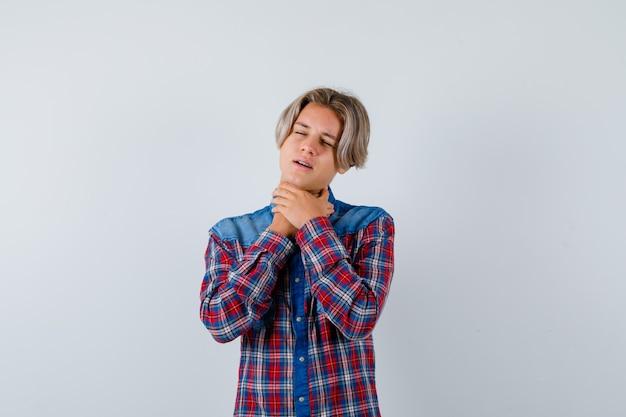 Jovem rapaz adolescente sofrendo de dor de garganta com a camisa e parecendo incomodado, vista frontal.