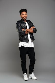 Jovem rapaz africano alegre na jaqueta de couro em pé com as mãos cruzadas, olhando