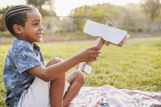 Jovem rapaz africano brincando com um brinquedo de madeira ao ar livre no parque da cidade - foco no rosto