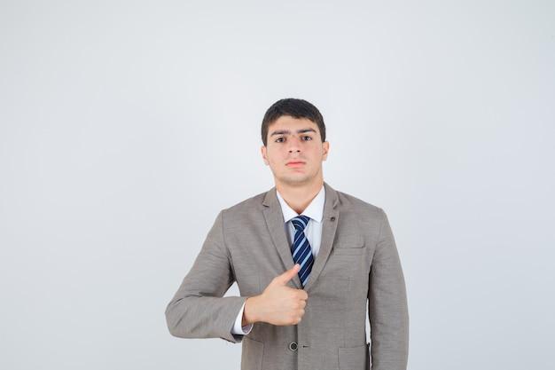 Jovem rapaz aparecendo o polegar em um terno formal e olhando sério, vista frontal.