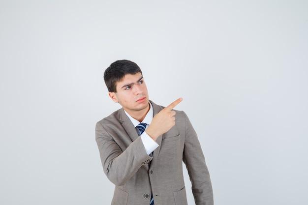 Jovem rapaz apontando para longe com o dedo indicador em um terno formal e olhando sério. vista frontal.