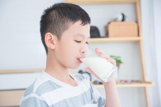 Jovem rapaz asiático beber um copo de leite no café da manhã