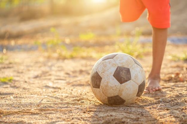 Jovem rapaz asiático brincando com bola de futebol clássico velho e sujo de manhã
