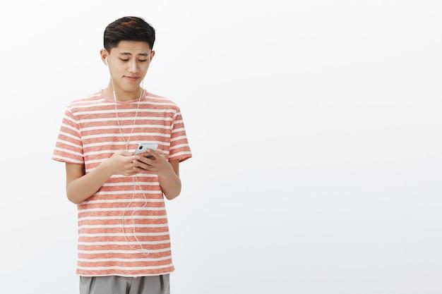 Jovem rapaz asiático com uma camiseta listrada segurando um smartphone usando fones de ouvido, parecendo um fofo e tocando a tela do celular