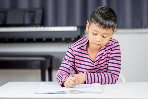 Jovem rapaz asiático escrever no caderno por lápis na sala
