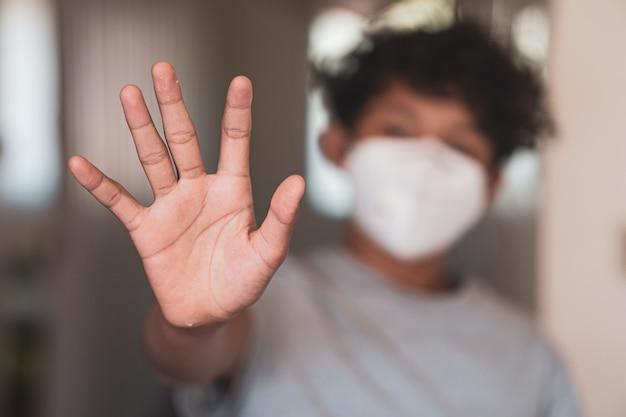 Jovem rapaz asiático, levantando a mão e usando uma máscara protetora, medo de parar a gripe e o coronavírus