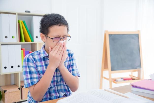 Jovem rapaz asiático limpa o nariz com um lenço de papel na sala de aula da escola