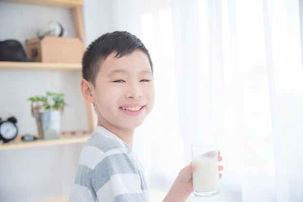 Jovem rapaz asiático segurando um copo de leite e sorrindo para a câmera