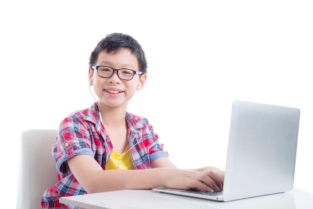 Jovem rapaz asiático usando fone de ouvido e usando o computador portátil sobre fundo branco
