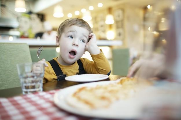 Jovem rapaz bocejando enquanto espera ser alimentado