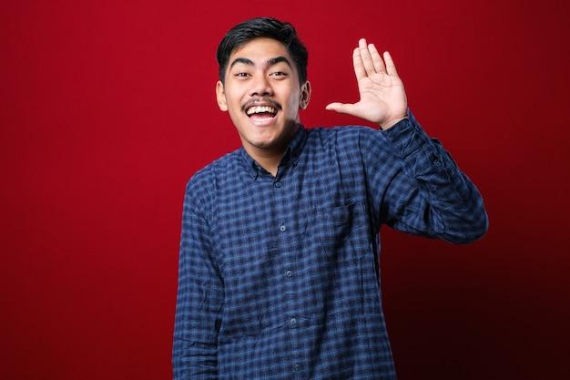 Jovem rapaz bonito asiático vestindo camiseta branca em pé sobre um fundo vermelho renunciando a dizer olá feliz e sorridente, gesto amigável de boas-vindas