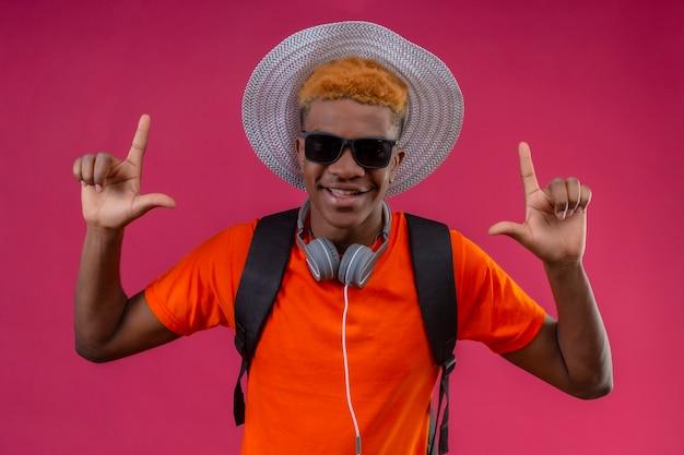 Jovem rapaz bonito com chapéu de verão com câmera e fones de ouvido feliz e positivo com dedos apontando em pé sobre a parede rosa