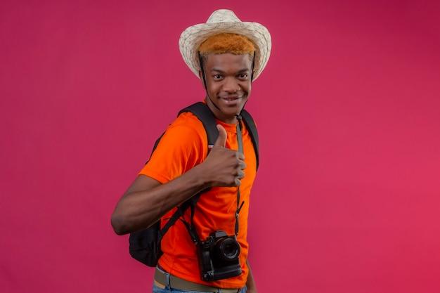 Jovem rapaz bonito com chapéu de verão com câmera feliz e positiva mostrando os polegares em pé sobre a parede rosa