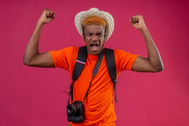 Jovem rapaz bonito com chapéu de verão e câmera com expressão de raiva levantando os punhos em pé sobre a parede rosa