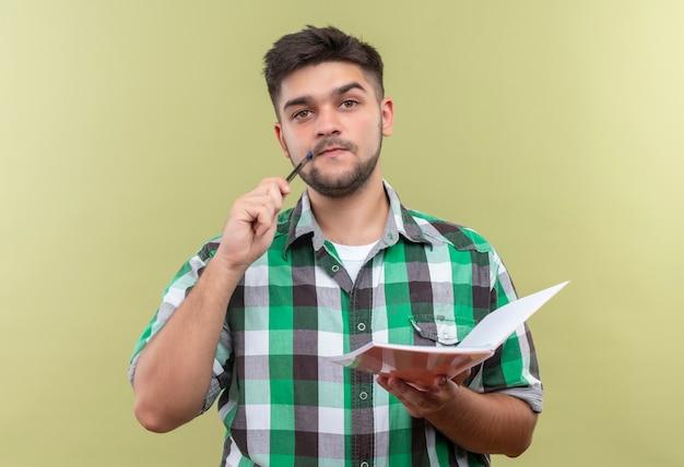 Jovem rapaz bonito de camisa quadriculada, olhando pensativamente, segurando a caneta com o mouse em pé sobre a parede cáqui