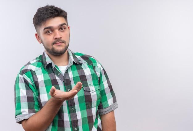 Jovem rapaz bonito de camisa quadriculada perguntando o que há de novo em pé sobre uma parede branca