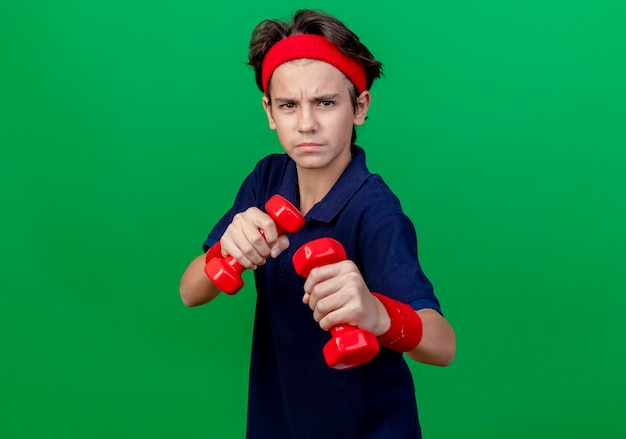 Jovem rapaz bonito desportivo carrancudo usando bandana e pulseiras com aparelho dentário segurando halteres, fazendo gesto de boxe isolado na parede verde com espaço de cópia