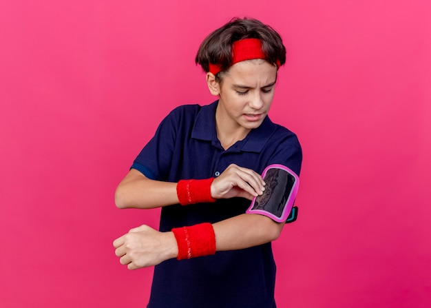 Jovem rapaz bonito e carrancudo, desportivo, usando fita para a cabeça, pulseiras e uma braçadeira de telefone com aparelho dentário tocando a braçadeira isolada na parede carmesim com espaço de cópia