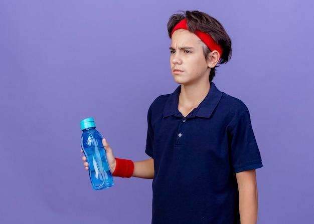 Jovem rapaz bonito e desportivo carrancudo usando bandana e pulseiras com aparelho dentário segurando uma garrafa de água, olhando diretamente isolado na parede roxa com espaço de cópia