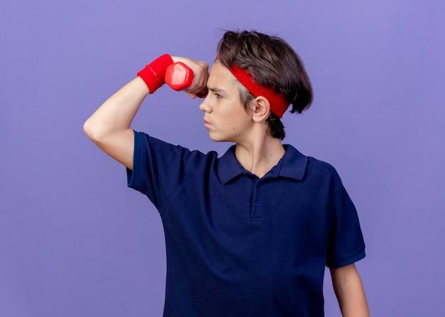 Jovem rapaz bonito e desportivo carrancudo usando bandana e pulseiras com aparelho dentário virando a cabeça para o lado segurando halteres fazendo um gesto forte isolado na parede roxa