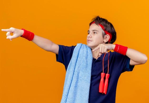 Jovem rapaz bonito e desportivo impressionado usando bandana e pulseiras com aparelho dentário e toalha com corda de pular nos ombros olhando e apontando para o lado isolado na parede laranja