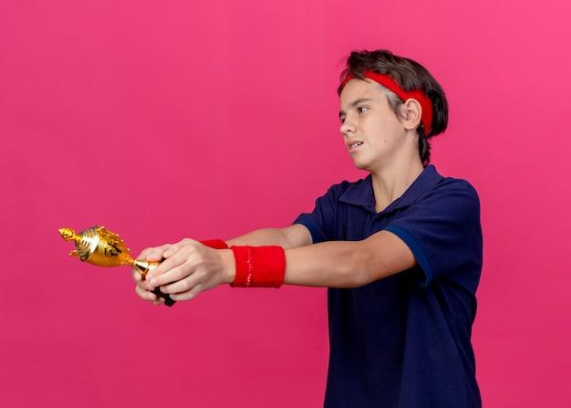 Jovem rapaz bonito e esportivo cansado usando bandana e pulseiras com aparelho dentário em pé em vista de perfil, estendendo-se para fora da taça do vencedor, olhando diretamente isolado no fundo vermelho