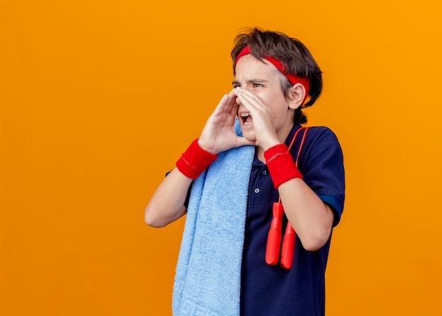 Jovem rapaz bonito e esportivo usando bandana e pulseiras com toalha e pular corda nos ombros, mantendo as mãos ao redor da boca chamando alguém isolado