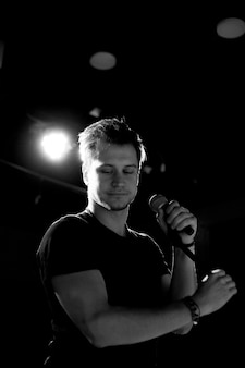 Jovem rapaz bonito emocionalmente canta e fala ao microfone. fotografia a preto e branco