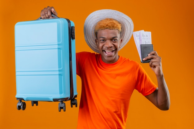 Jovem rapaz bonito satisfeito com uma camiseta laranja segurando uma mala de viagem e passagens de avião