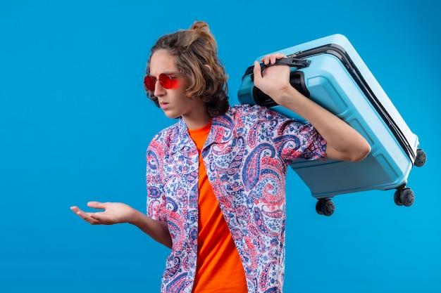 Jovem rapaz bonito usando óculos escuros vermelhos segurando uma mala de viagem, sem entender e confuso, sem resposta, estendendo os braços em pé sobre um fundo azul