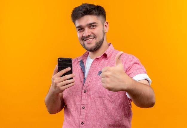 Jovem rapaz bonito vestindo uma camisa pólo rosa fazendo um feliz polegar para cima, segurando o telefone em pé sobre uma parede laranja