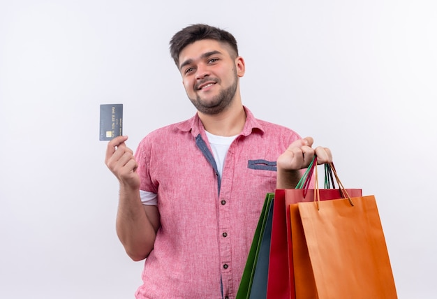Jovem rapaz bonito vestindo uma camisa pólo rosa feliz procurando fazer compras com um cartão de crédito em pé sobre uma parede branca
