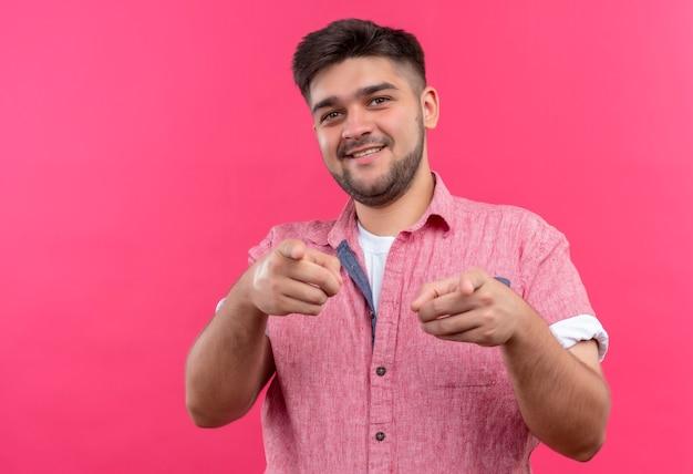 Jovem rapaz bonito vestindo uma camisa pólo rosa felizmente apontando para a câmera com os indicadores e fazendo oi você assinar em pé sobre a parede rosa